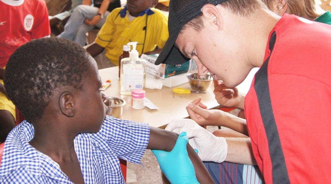 ガーナの子供の傷口を確認する高校生の医療ボランティア